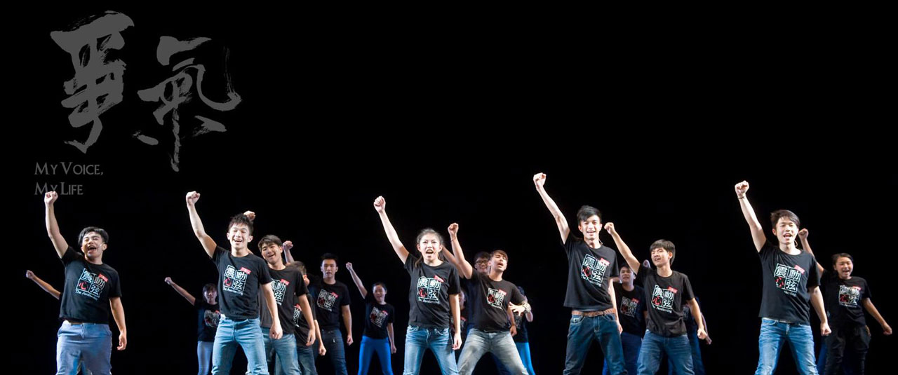 A scene from My Voice, My Life with the students on stage with right fists in the air